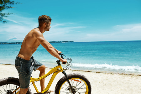 sporting activity: Summer Beach Sport. Athletic Man With Muscular Body Riding Yellow Sand Bicycle At Tropical Seaside. Fitness Male Model With Bike On Holiday Travel Vacation. Sporting Activity, Active Lifestyle Concept Stock Photo