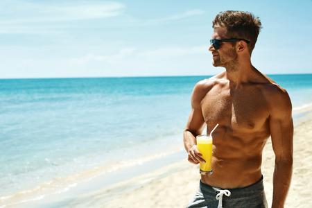 여름 휴식. 근육질의 몸이 열 대 해변에서 신선한 주스 스무디 칵테일을 마시는 운동 섹시한 남자의 초상화. 잘 생긴 휘트니스 남자 모델 일광욕, 휴가