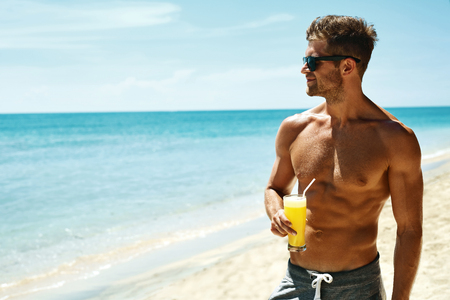 Summer Relax. Portrait Of Athletic Sexy Man With Muscular Body Drinking Fresh Juice Smoothie Cocktail On Tropical Beach. Handsome Fitness Male Model Sunbathing, Enjoying Refreshing Drink On Vacation Фото со стока - 57345517