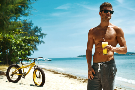 fit man: Summer Vacations. Man With Fit Sexy Body And Muscular Torso Drinking Fresh Juice Smoothie Cocktail On Tropical Beach After Riding Bicycle. Handsome Fitness Male Model Enjoying Refreshing Healthy Drink