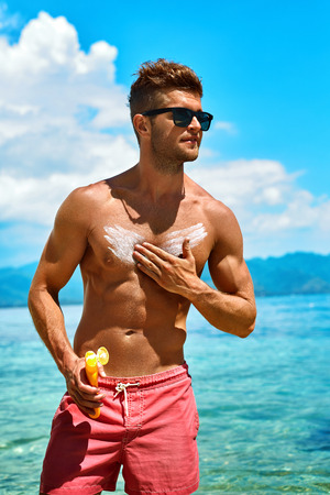 muscular body: Man Skin Care In Summer. Handsome Male With Sexy Body In Sunglasses Applying UV Protective Sunscreen Lotion Before Sunbathing, Tanning At Beach Using Solar Sun Block Protection Cream For Healthy Tan.