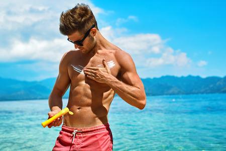 cuerpo hombre: Hombre Cuidado de la piel en verano. Varón hermoso con la carrocería atractiva en gafas de sol de protección UV Aplicación de loción de protección solar Antes de tomar el sol, bronceado en la playa El uso de crema solar Bloqueador solar Protección Para Tan sano.