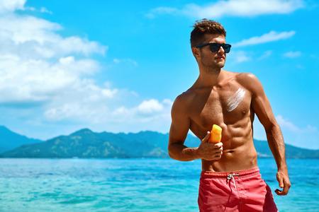 Protection de la peau du soleil en été. Handsome Man In Sunglasses Bain de soleil Avec Lotion Sur Sexy Body Musclé Athletic. Homme Fitness Model Tanning Utiliser Solar Bloc crème pour une saine Tan. Soin de la peau