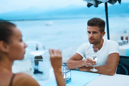 romantic evening with wine: Romantic Dinner. Happy Smiling Couple In Love Having Dinner At Sea Restaurant In Evening On Beach. Handsome Man And Beautiful Woman Drinking White Wine, Celebrating Holiday Or Relationship Anniversary Stock Photo