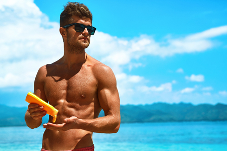 applying: Man Skin Care In Summer. Handsome Male With Sexy Body In Sunglasses Applying UV Protective Sunscreen Lotion Before Sunbathing, Tanning At Beach Using Solar Sun Block Protection Cream For Healthy Tan.