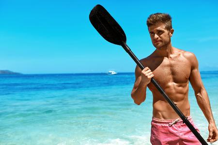 夏のウォーター スポーツ。カヤックはカヌーのパドルを保持している水着でセクシーな体にハンサムなアスレチック男。熱帯の海のビーチで楽しん