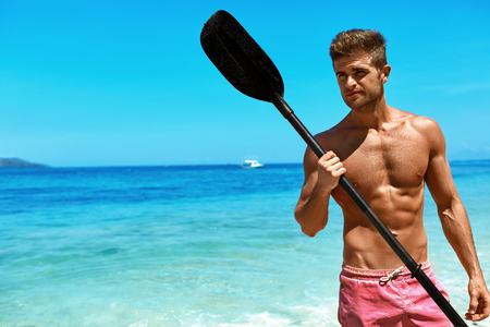 sporting activity: Summer Water Sport. Handsome Athletic Man With Sexy Body In Swimwear Holding Canoe Kayak Paddle. Beautiful Fitness Male Model Having Fun At Tropical Sea Beach. Recreational Leisure Sporting Activity Stock Photo