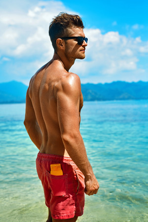 skin protection: Summer Travel Vacation. Handsome Man With Sexy Body In Fashionable Sunglasses Sunbathing, Tanning At Sea Beach. Fitness Male Model With Sunscreen Lotion, Sun Block Skin Protection Cream In Pocket Stock Photo