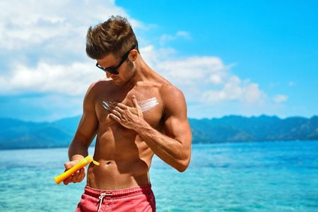 Man Skin Care In Summer. Handsome Male With Sexy Body In Sunglasses Applying UV Protective Sunscreen Lotion Before Sunbathing, Tanning At Beach Using Solar Sun Block Protection Cream For Healthy Tan.