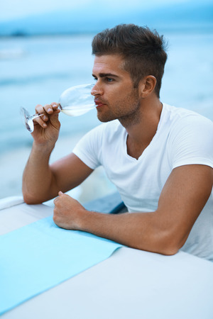 romantic evening with wine: Close Up Portrait Of Happy Handsome Romantic Young Man Drinking White Wine From A Glass And Having Dinner In Beach Restaurant In Evening, Enjoying Sea View On Summer Vacation. Drink Concept