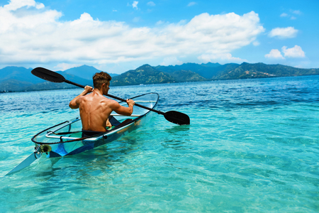 sporting activity: Summer Travel Kayaking. Man Paddling Transparent Canoe Kayak In Tropical Ocean, Enjoying Recreational Sporting Activity. Male Canoeing With Paddle, Exploring Sea On Vacation. Rowing Water Sports