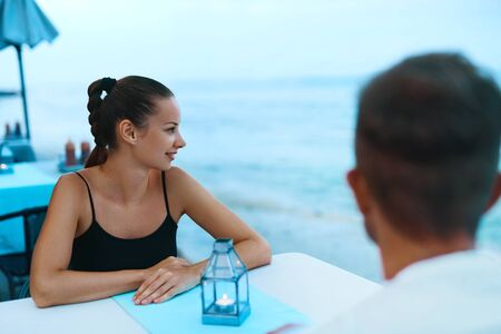 romantic beach: Romantic Dinner. Happy Smiling Couple In Love Having Dinner At Ocean Restaurant In Evening On Beach. Handsome Man And Beautiful Woman Enjoying Sea View Celebrating Holiday Or Relationship Anniversary Stock Photo