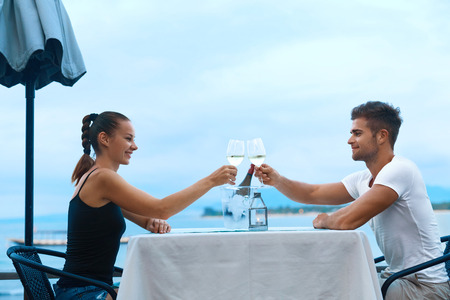 anniversary beach: Celebration. Happy Romantic Smiling Couple In Love Cheering With Glasses Of White Wine While Having Dinner At Sea Restaurant On Beach. Man And Woman Celebrating Relationship Anniversary. Cheers