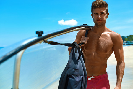 sporting activity: Summer Water Sport. Handsome Athletic Man With Sexy Body Holding Transparent Canoe Kayak. Beautiful Male Model Having Fun At Tropical Sea Beach. Travel Kayaking, Recreational Leisure Sporting Activity