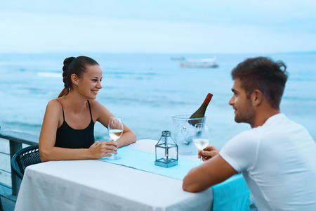 anniversary beach: Romantic Dinner. Happy Smiling Couple In Love Having Dinner At Sea Restaurant In Evening On Beach. Handsome Man And Beautiful Woman Drinking White Wine, Celebrating Holiday Or Relationship Anniversary Stock Photo