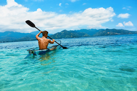 recreational sports: Summer Travel Kayaking. Man Paddling Transparent Canoe Kayak In Tropical Ocean, Enjoying Recreational Sporting Activity. Male Canoeing With Paddle, Exploring Sea On Vacation. Rowing Water Sports