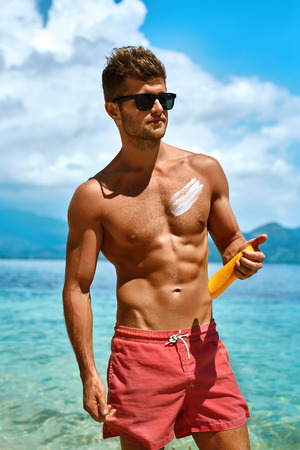 skin protection: Sun Skin Protection In Summer. Handsome Man In Sunglasses Sunbathing With Sunscreen Lotion On Sexy Athletic Muscular Body. Male Fitness Model Tanning Using Solar Block Cream For Healthy Tan. Skincare