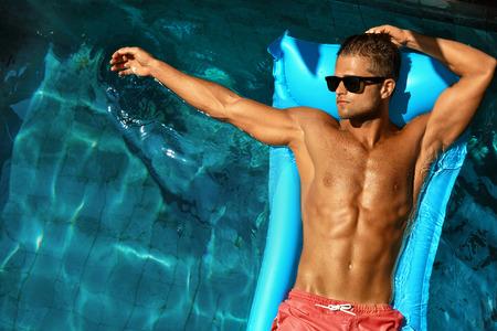 modelos hombres: El hombre del cuerpo en verano. Hombre en piscina. Modelo hermoso atractivo en gafas de sol que broncea en piscina de agua A Resort. Individuo apto Con Sun Tan saludable de la piel que se relaja en vacaciones Vacaciones. El verano Relax Foto de archivo
