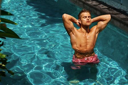 cuerpo hombre: Verano. Hombre Hermoso Con Sexy Body, Tan sano de la piel se relajan en piscina de agua sobre los viajes de vacaciones Vacaciones. Modelo masculino recibir placer De Sun Tanning En Relax Resort Spa Hotel. Disfrute