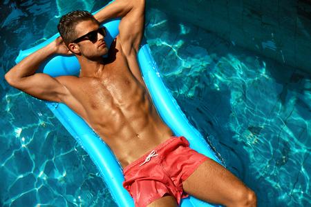 Man Summer Fashion. Schöner Mann mit sexy Körper in Badebekleidung, modische Sonnenbrille Tanning, schwimmend im Schwimmbadwasser im Relax Spa Resort. Fitness-Modell mit Haut Sun Tan auf Ferien sich entspannt Lizenzfreie Bilder