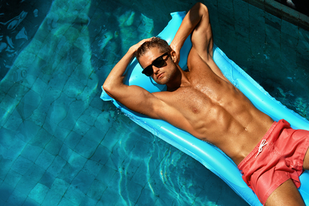 Summer Man Body Sun Skin Care. Beautiful Model With Sexy Body In Swimwear Tanning, Floating On Mattress In Swimming Pool Water. Fitness Male With Healthy Tan Relaxing At Relax Spa Resort. Summertime