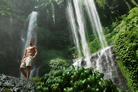 waterfall model: Water. Healthy Man Relaxing Near Beautiful Paradise Green Waterfall. Handsome Fitness Model With Sexy Fit Body, Wet Skin Enjoying Nature Beauty On Summer Travel Vacation. Health Care, Sport Concept Stock Photo