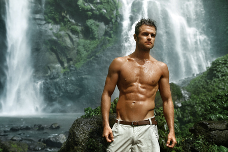 nature beauty: Water. Healthy Man Relaxing Near Beautiful Paradise Green Waterfall. Handsome Fitness Model With Sexy Fit Body, Wet Skin Enjoying Nature Beauty On Summer Travel Vacation. Health Care, Sport Concept Stock Photo