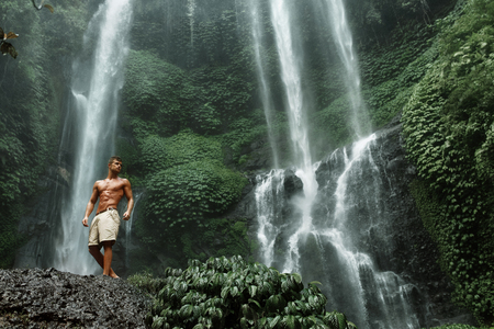 Water. Healthy Man Relaxing Near Beautiful Paradise Green Waterfall. Handsome Fitness Model With Sexy Fit Body, Wet Skin Enjoying Nature Beauty On Summer Travel Vacation. Health Care, Sport Concept Banque d'images