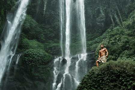 beautiful body: Water. Healthy Man Relaxing Near Beautiful Paradise Green Waterfall. Handsome Fitness Model With Sexy Fit Body, Wet Skin Enjoying Nature Beauty On Summer Travel Vacation. Health Care, Sport Concept Stock Photo