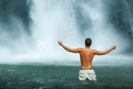 waterfall: Freedom Man. Free Happy Healthy Male Relaxing In Pure Water Near Beautiful Paradise Waterfall With Hands Up, Enjoying Rain Forest Nature Beauty On Travel Vacation. Enjoyment, Health, Wellness Concept Stock Photo