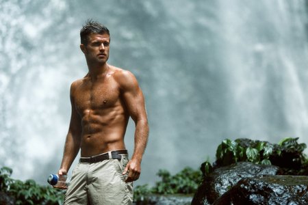 Water Drink. Healthy Man With Sexy Fit Body Holding Bottle Of Fresh Pure Water, Enjoying Nature Near Beautiful Tropical Paradise Waterfall On Summer Travel Vacation. Health Care, Hydration Concept Banque d'images