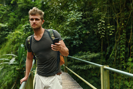 using phone: Man Using Mobile Phone For Communication. Tourist Male Holding Smartphone On Summer Travel Vacation. Beautiful Handsome Happy Traveler Enjoying Tropical Forest Nature. Tourism, Technology Connection.