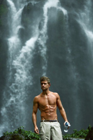 hydration: Water Drink. Healthy Man With Sexy Fit Body Holding Bottle Of Fresh Pure Water, Enjoying Nature Near Beautiful Tropical Paradise Waterfall On Summer Travel Vacation. Health Care, Hydration Concept Stock Photo