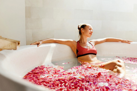 aroma: Woman In Bath At Day Spa Salon. Beautiful Smiling Girl In Bikini Bathing, Bathe With Flower Petals In Summer. Sexy Female Relaxing Outdoors. Aroma Therapy Beauty Treatment, Body Care. Relax Concept
