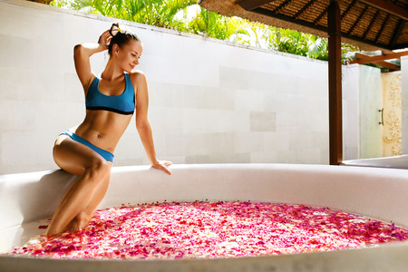 bathing beauty: Day Spa Body Care. Beautiful Sexy Happy Woman With Healthy Skin In Bikini Relaxing Near Round Outdoor Bath With Tropical Flower Petals, Enjoying Summer. Bathing Beauty Treatment, Aroma Therapy, Health Stock Photo