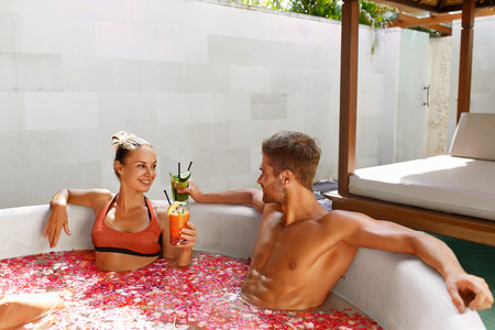 mujer bañandose: Vacaciones románticas. Pares en el amor que se relaja, se baña en flor al aire libre baño en el Día de lujo del salón del balneario. Feliz el hombre y la mujer hermosa potable fresca Detox cóctel de jugo de bebida. El verano se relaja, Relaciones