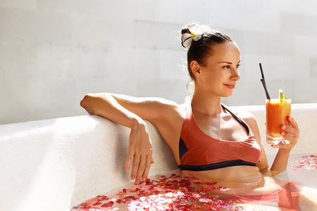 summer diet: Detox Diet And Summer Relax. Beautiful Sexy Happy Smiling Woman Drinking Fresh Detox Juice Cocktail, Healthy Drink While Bathing, Relaxing In Outdoor Flower Bath In Luxury Day Spa Salon On Vacation
