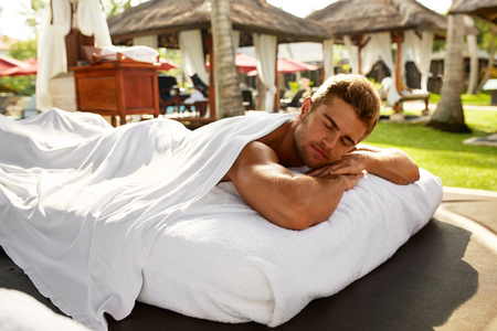 relax massage: Spa For Man. Beautiful Healthy Happy Male Model Relaxing At Day Spa Beauty Salon. Handsome Guy Enjoying Summer Body Relaxation Treatment, Lying On Relax Massage Table Outdoors. Health Care Concept