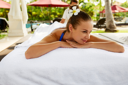 relax massage: Spa For Woman. Beautiful Smiling Woman Relaxing At Day Spa Beauty Salon. Healthy Happy Girl Enjoying Summer Body Relaxation Massage, Lying On Table Outdoors. Health Care, Pamper, Relax Concepts Stock Photo