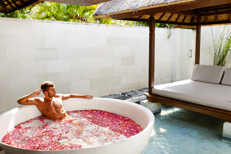 aroma therapy: Man Relaxing In Spa Bath. Beautiful Handsome Healthy Male With Sexy Body Bathing, Bathe In Tropical Flower Petals Outdoor Tub, Enjoying Summer Aroma Therapy Beauty Treatment In Day Spa Salon. Relax