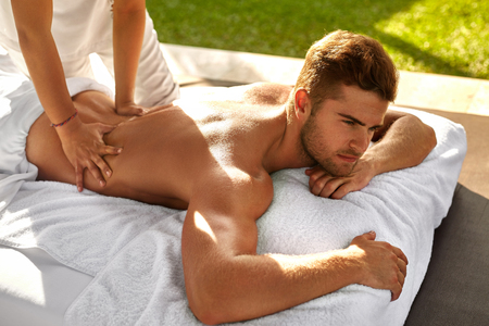 aromas: Spa Massage For Man. Close Up Of Handsome Healthy Smiling Man Enjoying Relaxing Back Massage At Outdoor Beauty Salon. Masseuse Massaging Male Body With Aromatherapy Oil. Skin Care Treatment Concept