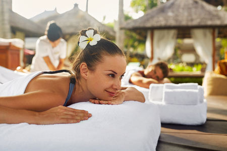 health resort treatment: Spa Couple Massage. Beautiful Happy Smiling Woman And Healthy Man Enjoying Relaxing Body Massage Treatment Outdoors At Beauty Salon. People At Romantic Day Spa Resort. Health Care And Relax Concept