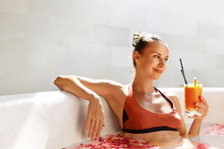 mujer bañandose: Detox Diet And Summer Relax. Beautiful Sexy Happy Smiling Woman Drinking Fresh Detox Juice Cocktail, Healthy Drink While Bathing, Relaxing In Outdoor Flower Bath In Luxury Day Spa Salon On Vacation
