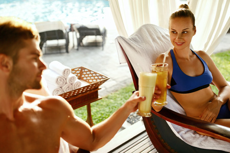 couple outdoor: Couple In Love On Romantic Vacation At Day Spa Resort. Happy Smiling Man, Beautiful Woman Cheering With Cocktail Drinks, Relaxing In Outdoor Tent, Celebrating Anniversary On Summer Honeymoon Travel.