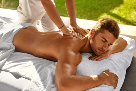 Spa Body Massage. Close Up Beautiful Sexy Healthy Happy Man Enjoying Relaxing Back Massage In Outdoor Day Beauty Salon. Masseur Hand Massaging Male With Aromatherapy Oil. Skin Care Treatment Concept Stock Photo