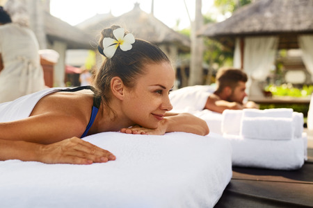 relax massage: Romantic Couple Spa. Closeup Of Beautiful Healthy Happy Smiling Woman, Handsome Man Relaxing At Day Spa Resort. People Enjoying Body Relaxation Massage Outdoors In Summer. Relax Treatment Concept