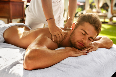 masseuse: Spa Massage For Man. Close Up Of Handsome Healthy Smiling Man Enjoying Relaxing Back Massage At Outdoor Beauty Salon. Masseuse Massaging Male Body With Aromatherapy Oil. Skin Care Treatment Concept