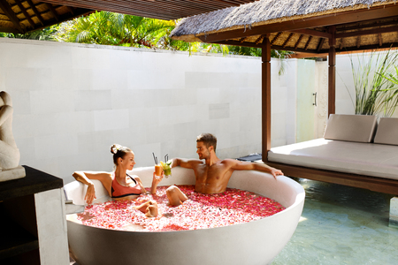 bathing man: Romantic Vacation. Couple In Love Relaxing, Bathing In Outdoor Flower Bath At Luxury Day Spa Salon. Happy Man And Beautiful Woman Drinking Fresh Detox Juice Cocktail Drink. Summer Relax, Relationships Stock Photo