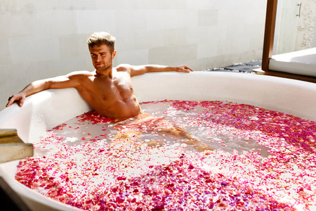 bathing man: Man Relaxing In Spa Bath. Beautiful Handsome Healthy Male With Sexy Body Bathing, Bathe In Tropical Flower Petals Outdoor Tub, Enjoying Summer Aroma Therapy Beauty Treatment In Day Spa Salon. Relax