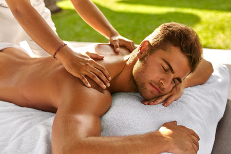 Spa Massage For Man. Close Up Of Handsome Healthy Smiling Man Enjoying Relaxing Back Massage At Outdoor Beauty Salon. Masseuse Massaging Male Body With Aromatherapy Oil. Skin Care Treatment Concept